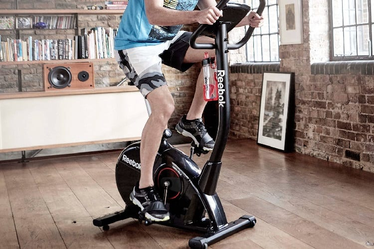 young fit man on upright bike