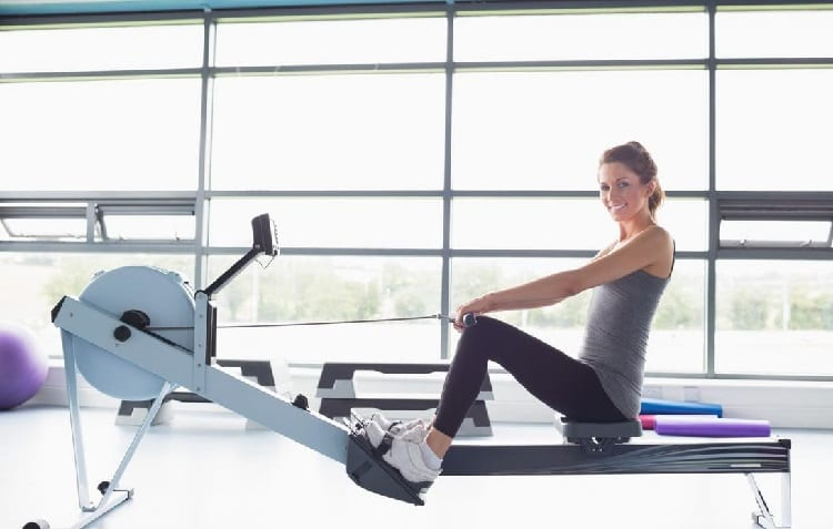 young sporty woman exercise on rowing machine