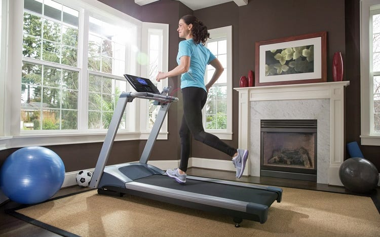 fit woman running on tradmill at home